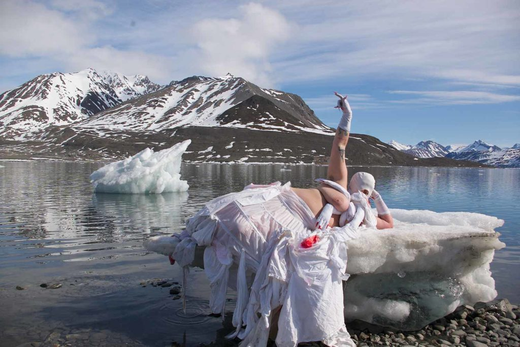 Linda Stupart poses divine upon a chunk of ice at the edge of a lake