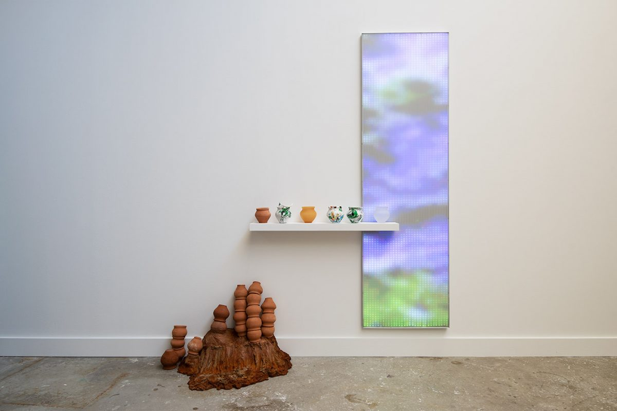 A pile of clay jars beneath a shelf next to a digital window