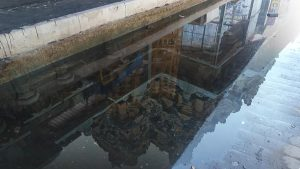 A cityscape as reflected in a puddle