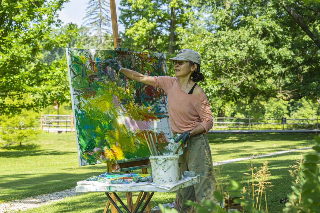 Ying Li painting outdoors on Haverford's campus