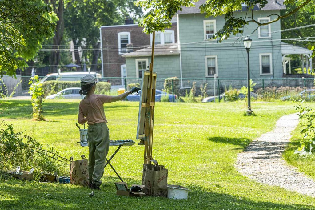 Ying Li painting outside with canvas, easel, and brushes