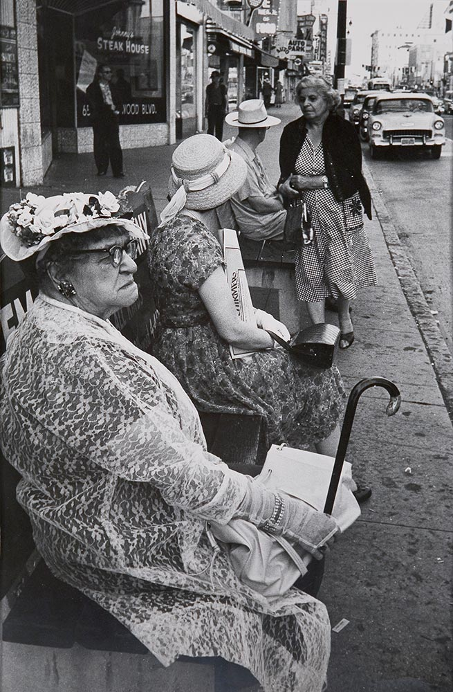 Women in hats sitting and waiting for a bus
