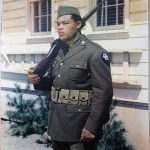 Joe Louis standing in at attention in his Army uniform