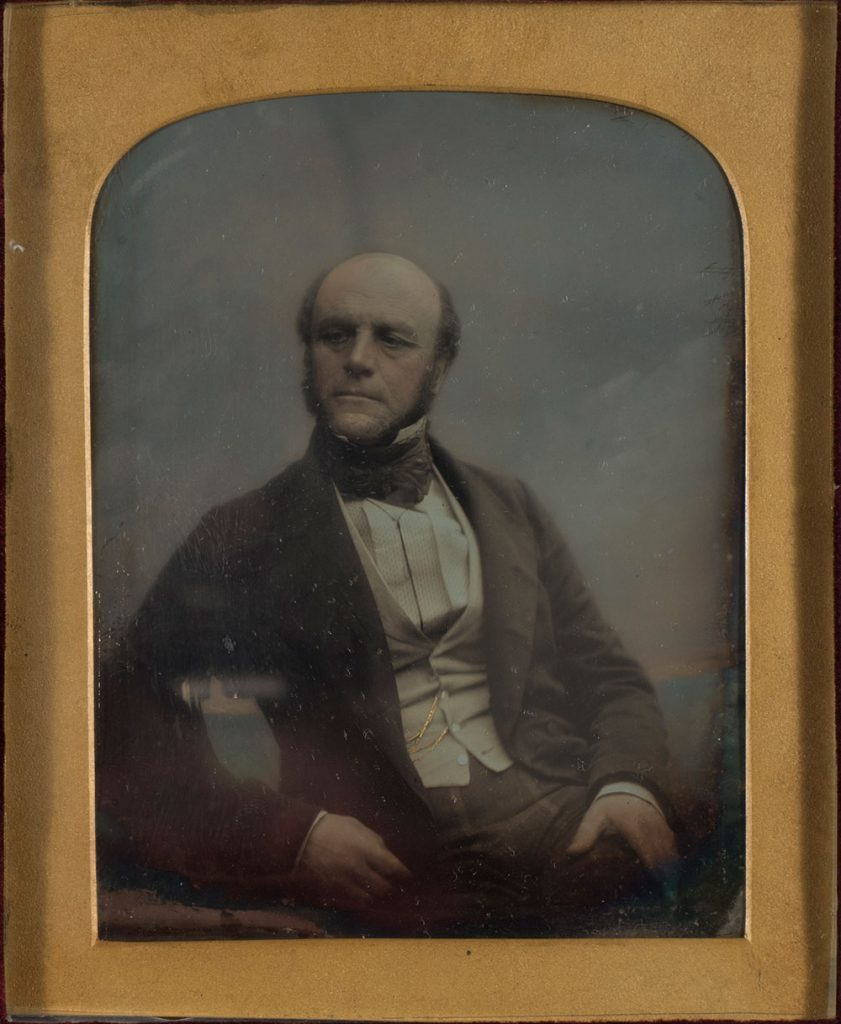 A man from the 1800s sits for a photograph