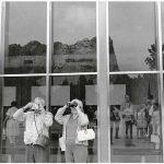 Tourists viewing Mount Rushmore through binoculars