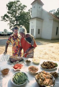 Edna at a table of food with a church visible in the background