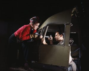 A woman and man riveting a cockpit