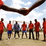 Men in a circle holding hands on a football field