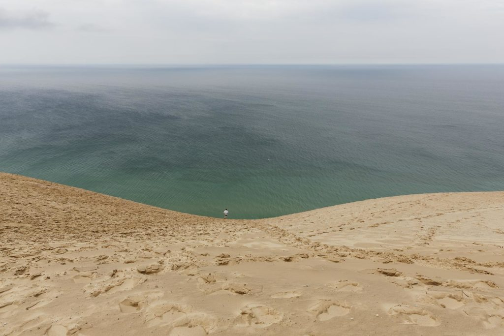 a boy in the distance at the bottom of a long plunge down a dune into water
