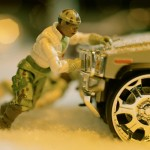 A G.I. Joe action figure peers from behind a Hummer in the snow.