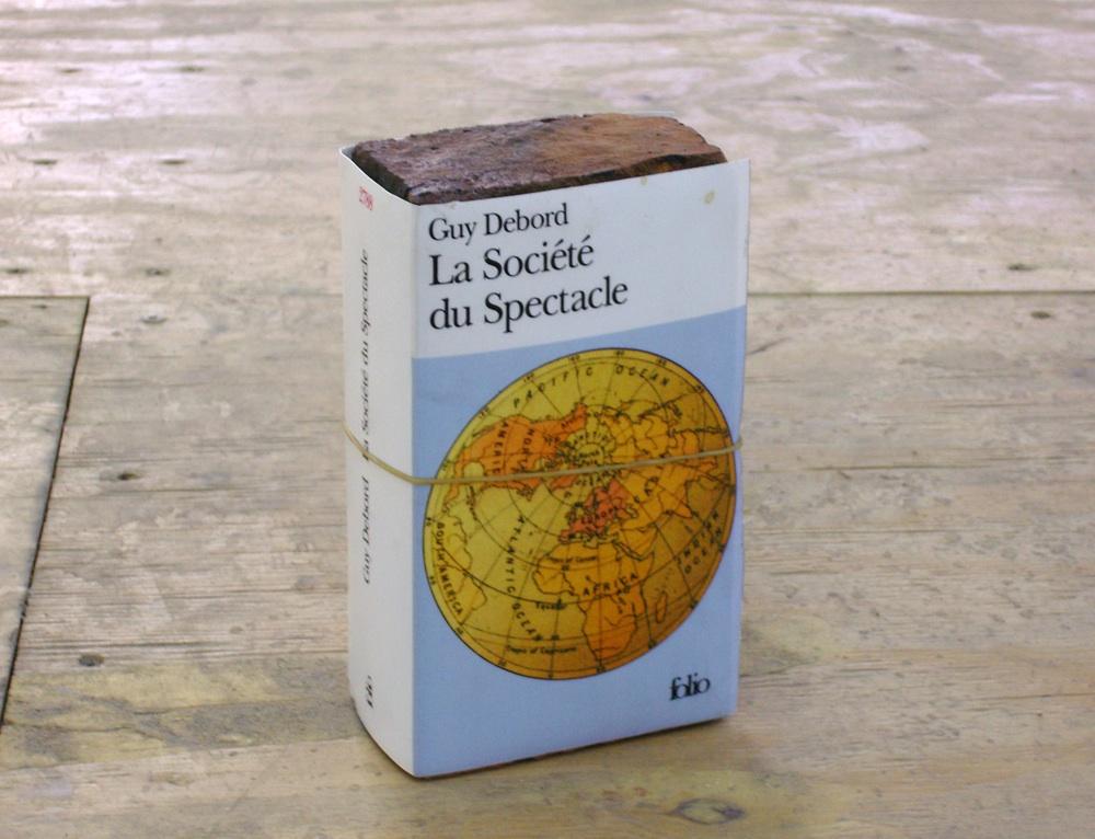 "Claire Fontaine  La sociéte du spectacle brickbat, 2005 Brick, archival digital brick, elastic band and glue  7 ½ x 4 1/3 x 2 ½"" Courtesy the artist"