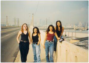 A group of women posing on a bridge