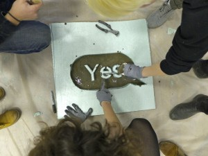 Students partake on the final step: pouring the concrete mixture into their mold.  Photo by John Muse.