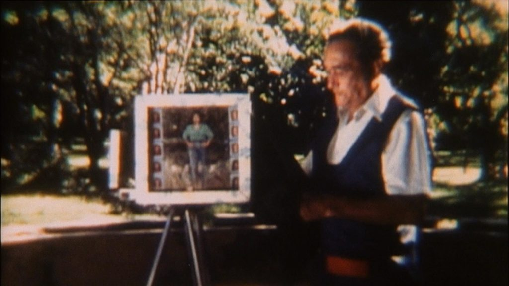 distorted older photograph of an old man standing beside an easel with another photograph displayed