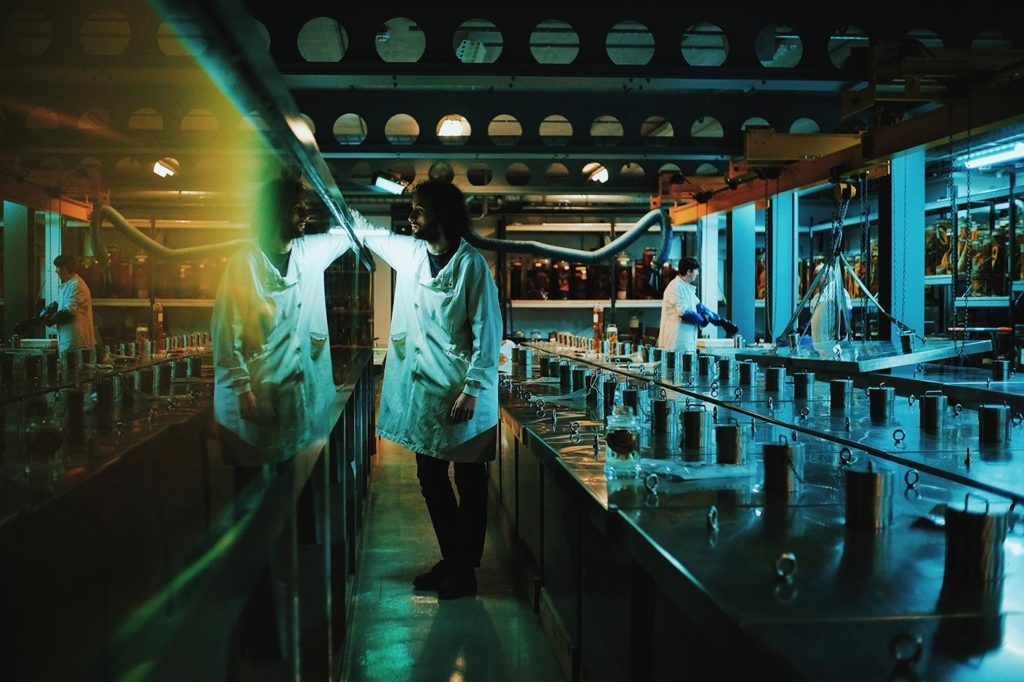 two men working in an eerily lit lab with jars everywhere