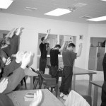 Prisoners standing with hands up in the air, facing away from the camera.