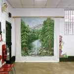 A backdrop of a forest hangs on a wall where photos are taken within Woodbourne Correctional Facility