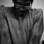 A male prisoner looking down with arms muscles tensed, covered in tattoos and scars.