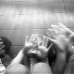 Black & white photo of girls holding hands up, obscuring their faces.