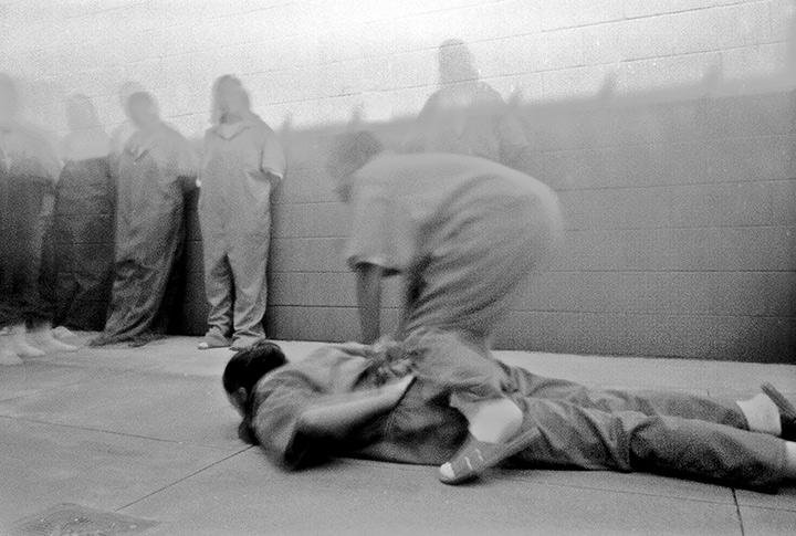 Black and white photo of a prisoner being restrained on the ground by another prisoner.