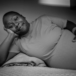 A pregnant female prisoner lying in her bunk, smiling at the camera.