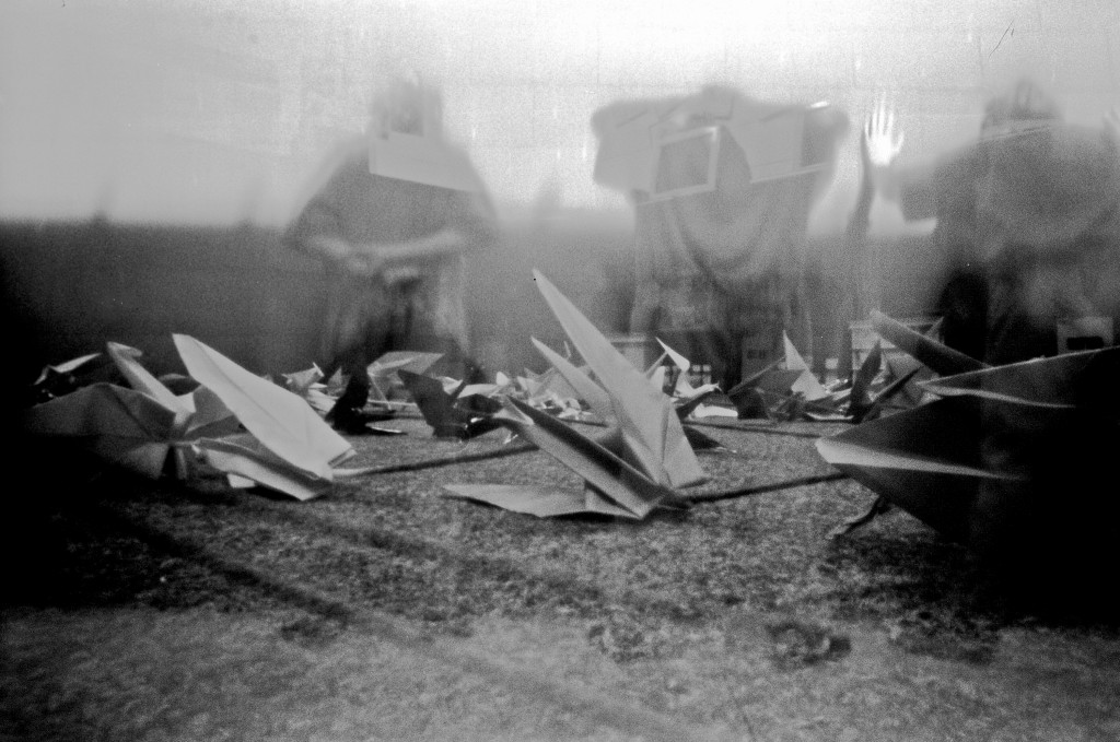 Black and white photo of paper cranes with foggy, obscured prisoners seated behind them.