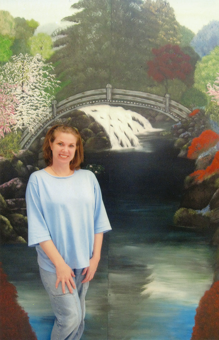 A female prisoner poses in front of a backdrop featuring a bridge and stream.