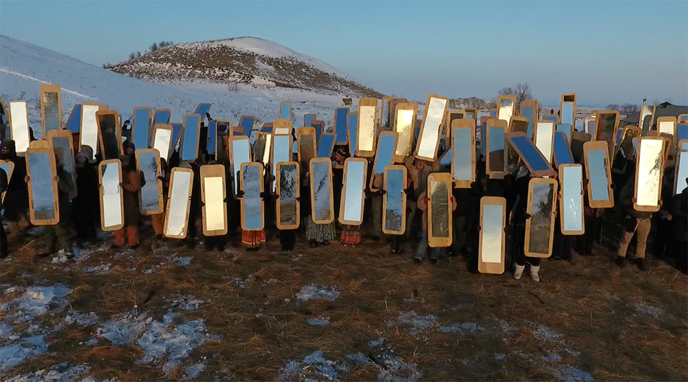 A group of people holding body-length mirrors atop a mountain reflecting light