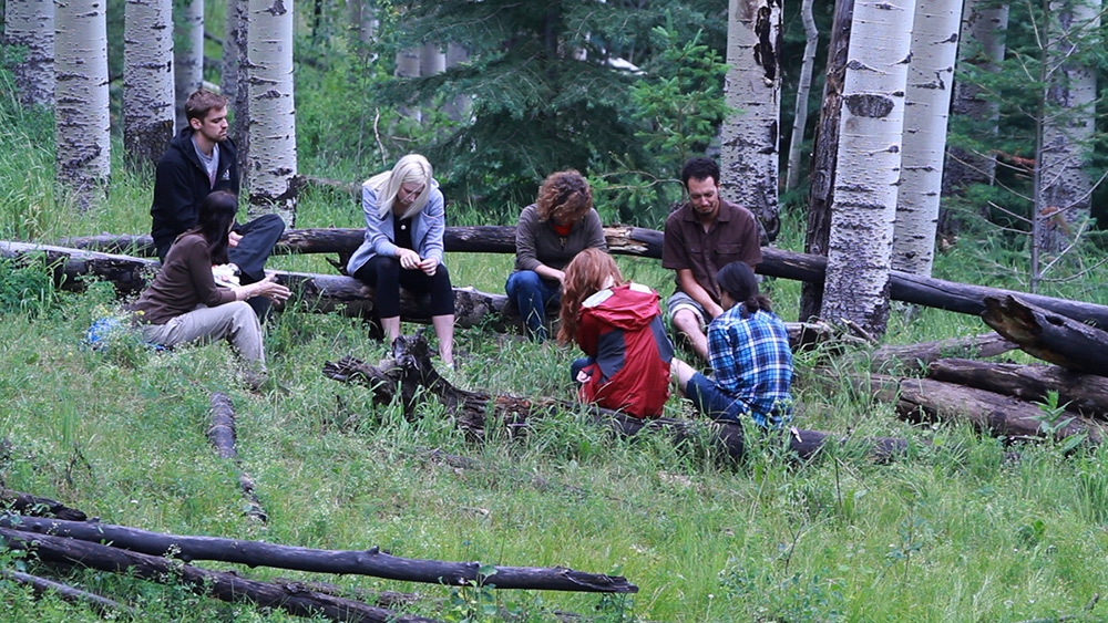 A group of people seated in a circle in the woods