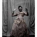 A black woman in victorian dress wearing a blindfold with hands up in the air