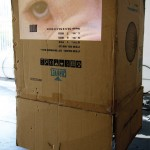 A large cardboard box with black tape and the image of an eye staring out at you.