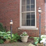View of brick house with window positioned between two lampposts; one is short, the other is tall.